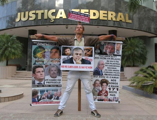 O mineiro André Rhouglas protesta amarrado a uma cruz em frente à sede da Justiça Federal, em Curitiba (PR)