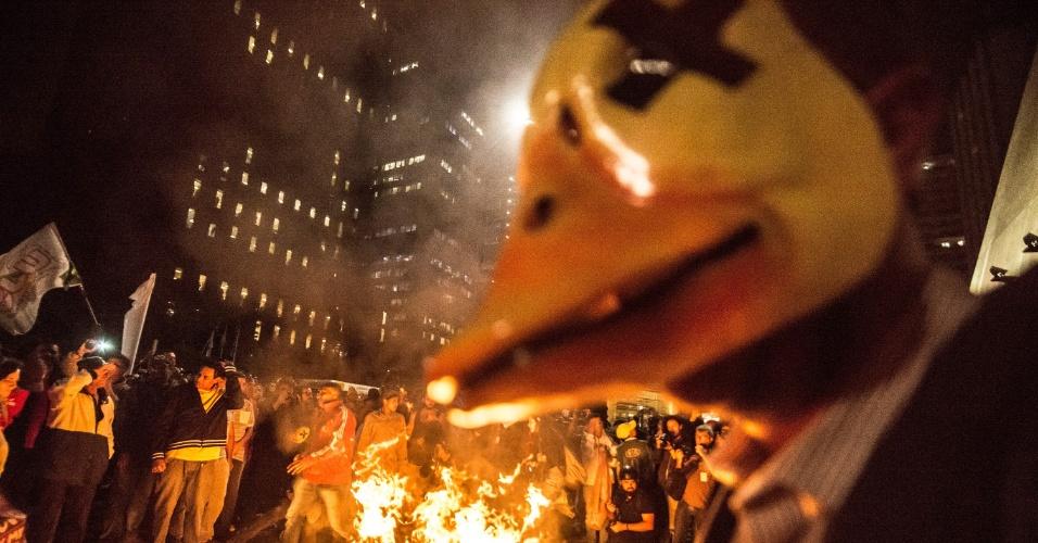 12.mai.2016 - Com máscara de um pato com olhos fechados, em ironia à campanha da Fiesp pelo impeachment da presidente Dilma (PT), homem se posiciona perto de fogueira feita na avenida Paulista, em São Paulo, durante protesto contra o governo Dilma