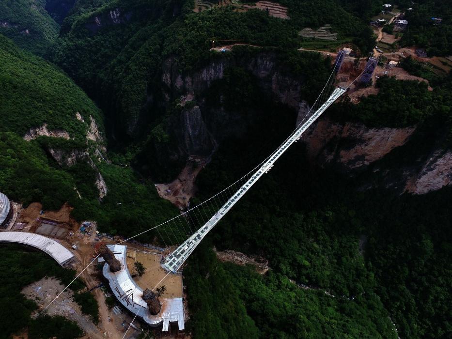 17.mai.2016 - Foto aérea mostra a ponte de vidro prestes a ser inaugurada sobre o Grande Cânion do Parque Nacional da Floresta de Zhangjiajie, na região central da China. Com 430 metros de comprimento e seis de largura, a ponte deve entrar em operação ainda no mês de maio. A estrutura foi submetida a mais de 100 testes para suportar em segurança o peso de até 800 pessoas simultaneamente
