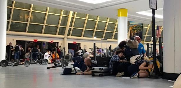 14.ago.2016 - Passageiros se deitam na área do controle de imigração após boato de tiroteio no Aeroporto Internacional JFK, em Nova York