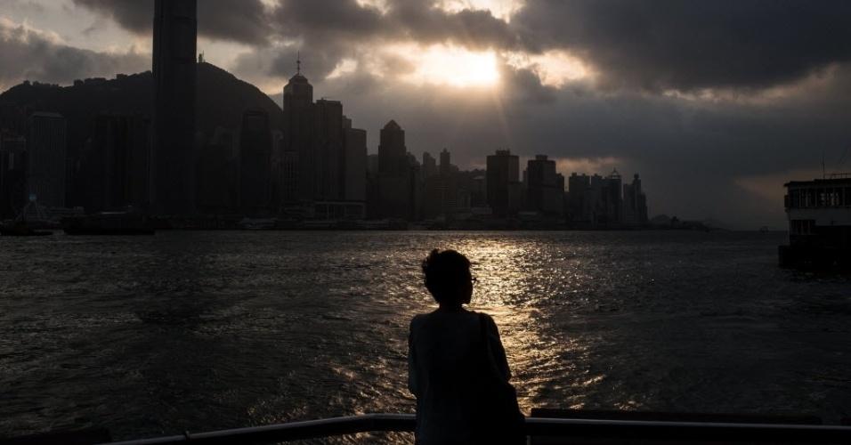 29.out.2016 - Mulher observa o sol se pôr no porto de Vitória, em Hong Kong