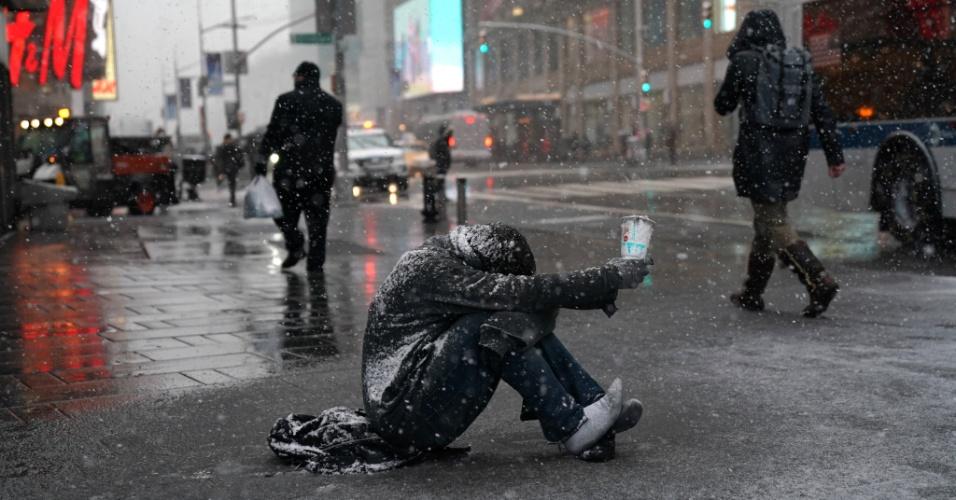 21.mar.2018 - Na neve, homem pede dinheiro na Times Square, em Nova York, EUA