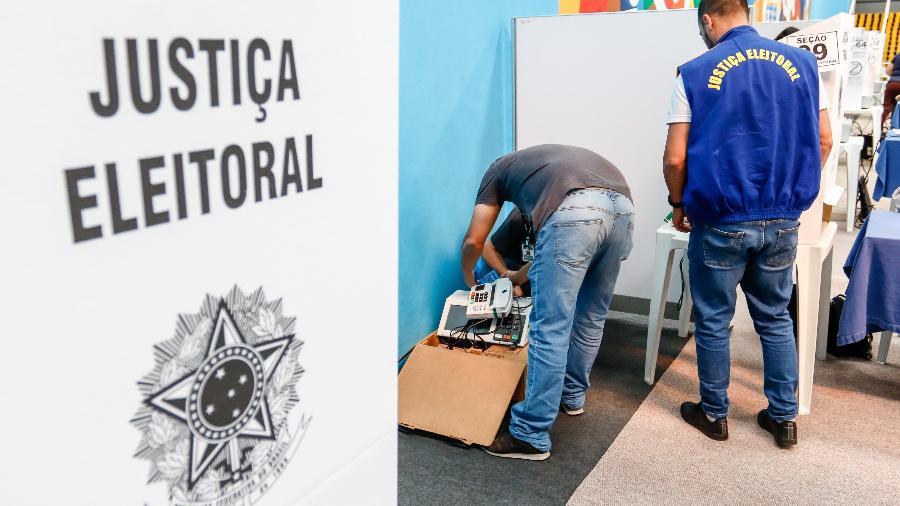 Funcionários da Justiça Eleitoral instalam urna eletrônica utilizada nas eleições de 2018 - Theo Marques/FramePhoto/FOLHAPRESS