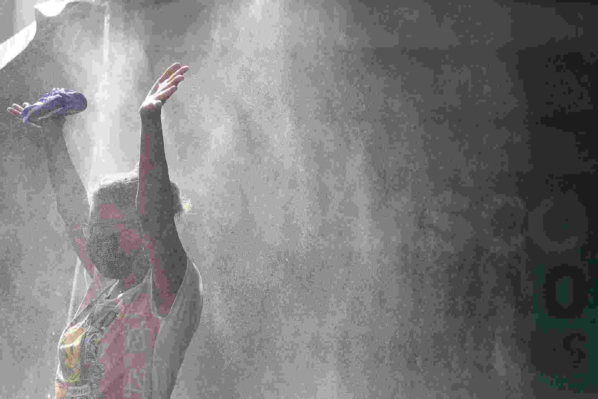 Uma mulher passa por um spray de solução desinfetante na entrada de uma estação de trem durante o surto de doença por coronavírus em Osasco - RAHEL PATRASSO/REUTERS