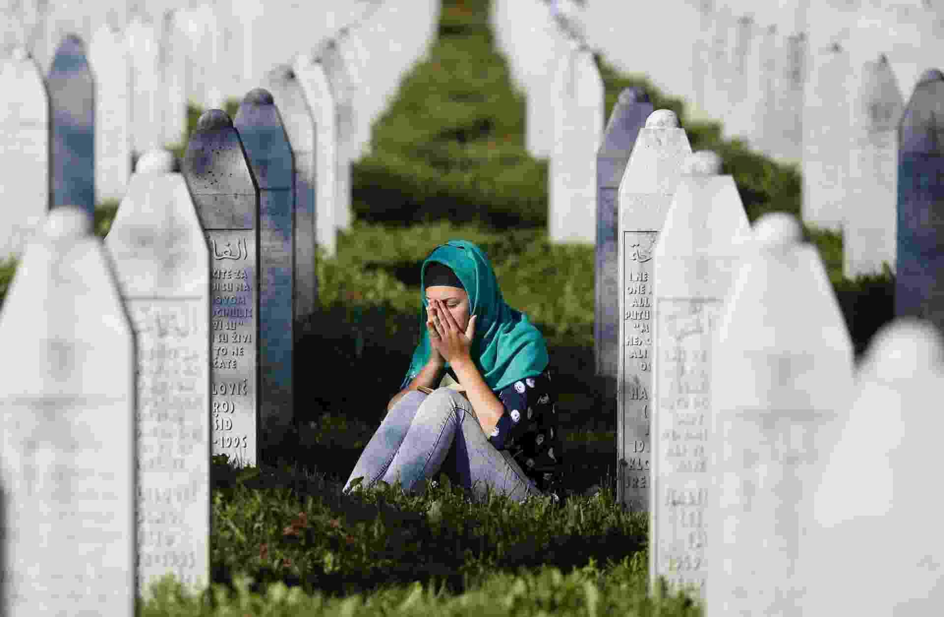 11.jul.2015 - Jovem visita túmulo de um parente no Centro Memorial de Potocari, no leste da Bósnia-Herzegóvina, no dia em que o país lembra os 20 anos de genocídio em Srebrenica. Ao todo, 136 recém-identificados muçulmanos bósnios foram enterrado como parte da cerimônia que marca o aniversário do maior crime cometido na Europa depois da Segunda Guerra Mundial - Dado Ruvic/Reuters