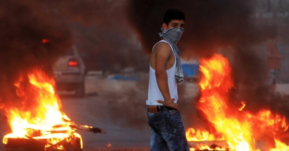 15.ago.2015 - Palestino anda próximo a pneus em chamas durante manifestação no vilarejo de Huwara, no sul da Cisjordânia, onde Ahmad Rafiq, 21, foi morto por forças de segurança israelense após esfaquear um policial de fronteira de Israel. Na manhã deste sábado, outro palestino foi baleado