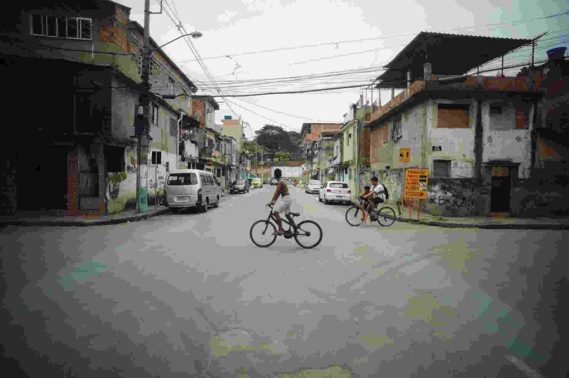 10.set.2015 - Ciclistas atravessam rua do Complexo da Maré, na zona norte do Rio de Janeiro, onde foram pintadas duas ciclofaixas - Fábio Teixeira/UOL