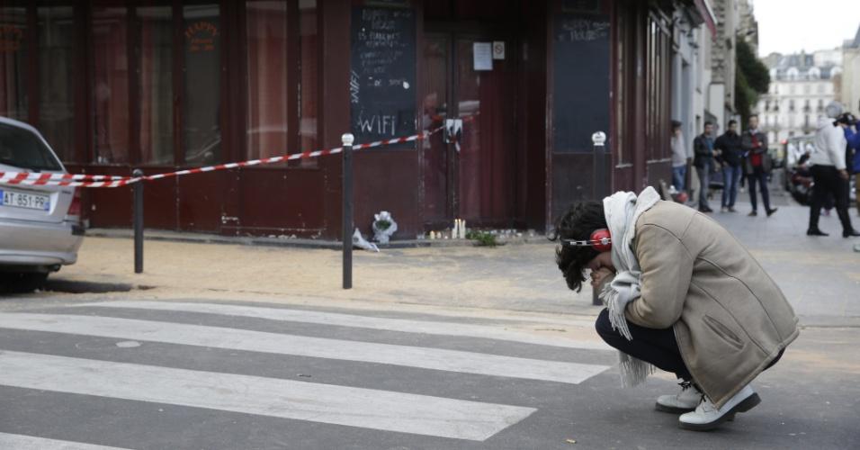 14.nov.2015 - Pessoa se emociona em um dos locais que sofreu ataques na véspera, no 10° distrito, em Paris