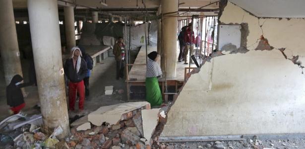 Populares inspecionam na cidade de Imphal o interior de prédio destruído pelo terremoto