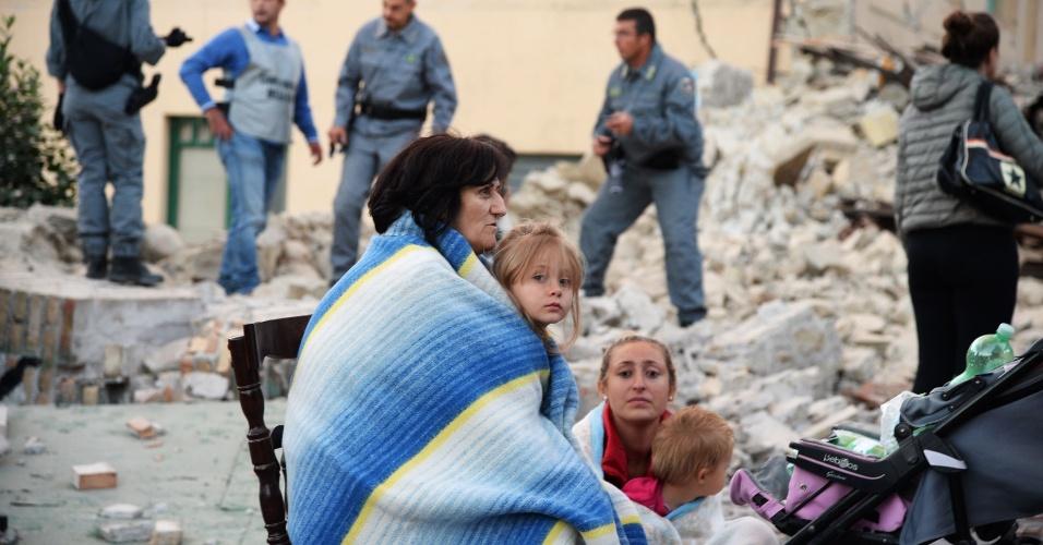 24.ago.2016 - Família observa os danos provocados pelo terremoto em Amatrice, na Itália. O tremor de magnitude 6,2 foi sentido em várias regiões do país