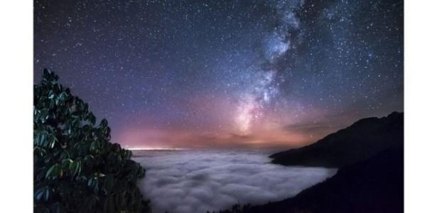 Na imagem, Via Láctea é retratada acima das nuvens do Himalaia, no Nepal, por Yevhen Samuchenko