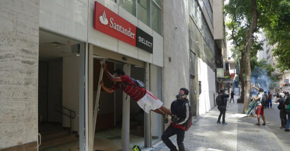 9.fev.2017 - Dois homens com máscaras depredam agência bancária durante confronto entre policiais e manifestantes nas imediações da Alerj, no centro do Rio