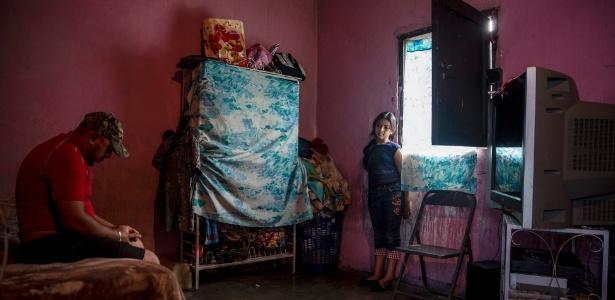 Eswin José Fuentes e sua filha em um quarto que eles dividem em San Pedro Sula, Honduras