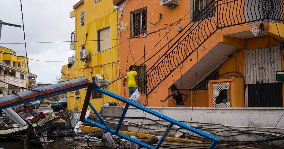 8.set.2017 - Pessoas caminham em meio aos destroços provocados pela passagem do furacão Irma pela ilha franco-holandesa São Martinho. A região foi uma das mais afetadas pelo fenômeno