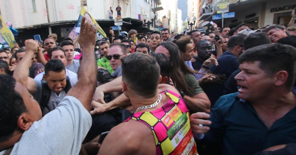 6.set.2018 - O homem (encoberto) suspeito de esfaquear o candidato à Presidência da República do PSL, Jair Bolsonaro, repreendido por pessoas após o atentado, ocorrido durante a campanha de Bolsonaro em Juiz de Fora (MG), na tarde desta quinta-feira, 6. Segundo entrevista rápida do porta-voz da Santa Casa da cidade, Bolsonaro teve uma perfuração na altura do abdômen. O candidato passa, neste momento, por um procedimento chamado laparotomia exploratória. Há suspeita de lesão no fígado e na alça intestinal