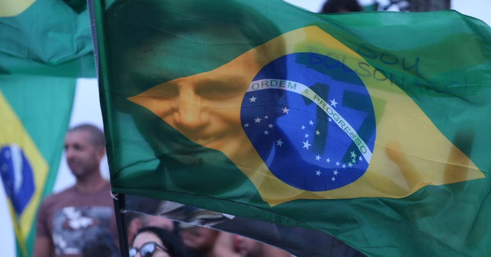 Apoiadora de Bolsonaro agita bandeira brasileira com o rosto do candidato