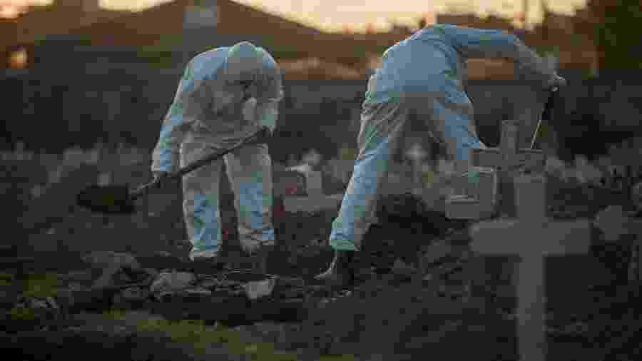 29.mai.2020 - Usando EPI, agentes do serviço funerário fazem sepultamento em cova rasa no Cemitério do Caju, no Rio de Janeiro - Allan Carvalho/AGIF/Estadão Conteúdo