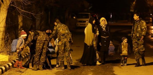 Sírios são auxiliados por membros das forças de segurança sírias após serem retirados de Madaya