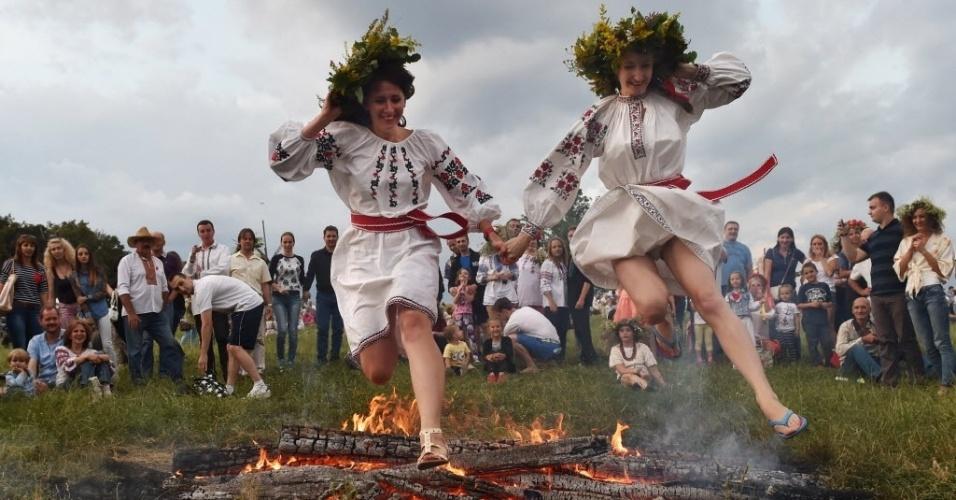 7.jul.2016 - Jovens usando roupas tradicionais ucranianas pulam uma fogueira durante a noite de Ivana Kupala, um antigo feriado pagão, no vilarejo de Pyrogove, próximo a Kiev, na Ucrânia. Durante as celebrações, as pessoas usam roupas típicas, pulam sobre fogueiras e tomam banho peladas em rios e lagos