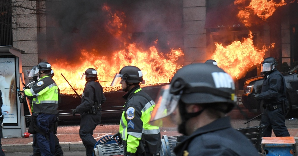 20.jan.2017 - Policiais tentam afastar manifestantes de limusine incendiada durante protestos pela posse do presidente Donald Trump em Washington