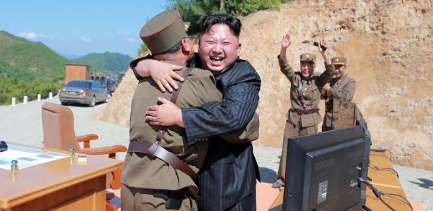 Imagem divulgada pela agência oficial norte-coreana KCNA mostra Kim Jong-un (de terno) comemorando o sucesso do teste intercontinental em um local não divulgado