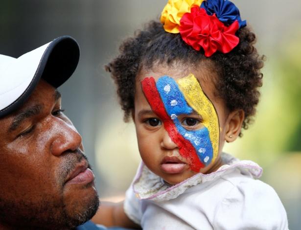 16.jul.2017 - Oposicionista carrega criança pintada com as cores da Venezuela durante plebiscito, em Caracas