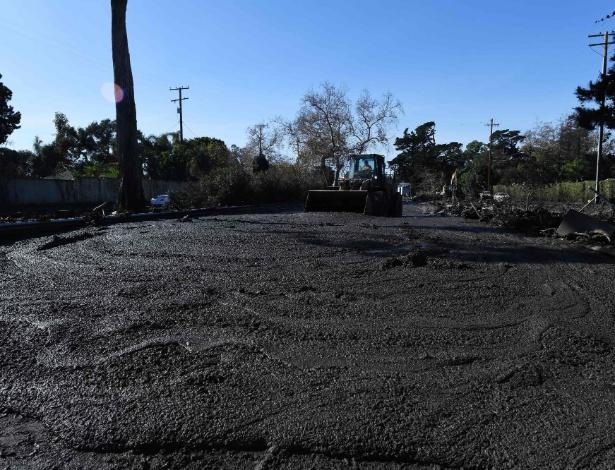 Máquina limpa a lama de rodovia perto de Montecito, depois do deslizamentos