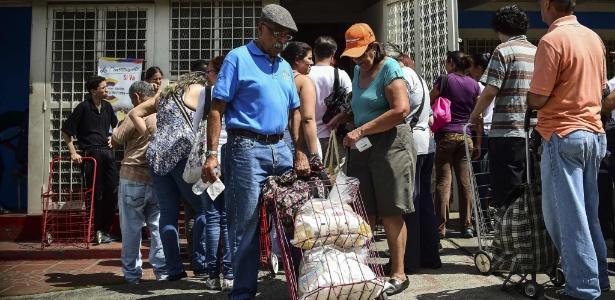 Homem empurra carrinho com alimentos distribuídos em Caracas, Venezuela - Ronald Schemidt/ AFP