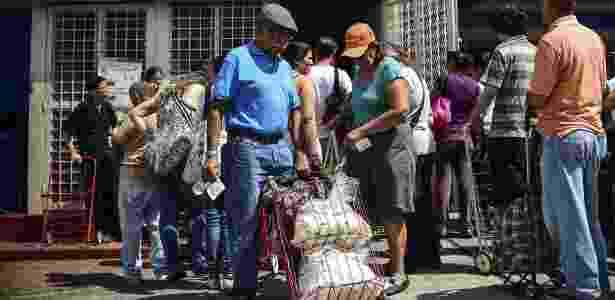 Homem empurra carrinho com alimentos distribuídos em um Clap, em Caracas - Ronald Schemidt/ AFP