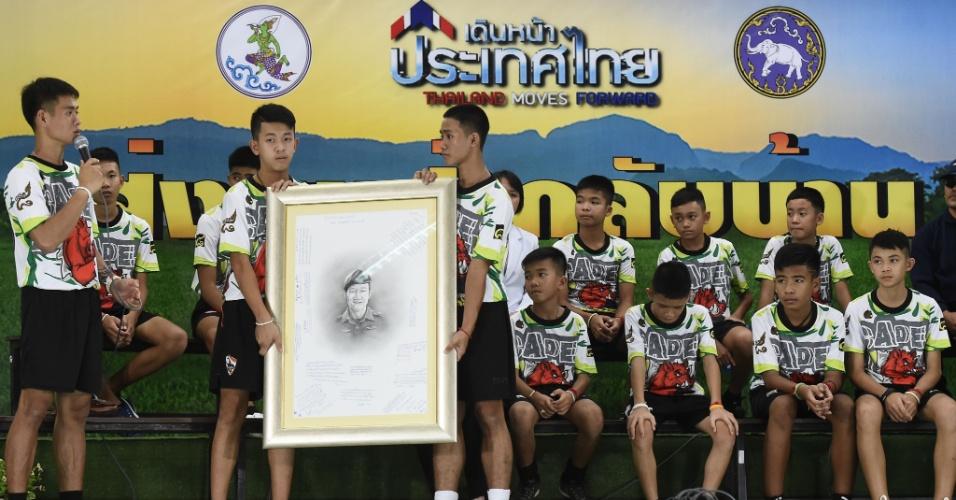 18.jul.2018 - O técnico de futebol tailandês, Ekkapol Chantawong (esquerda), com as 12 crianças restagatas prestam homenagem ao voluntário e ex-mergulhador Navy SEAL Saman Kunan, que morreu durante a operação de resgate