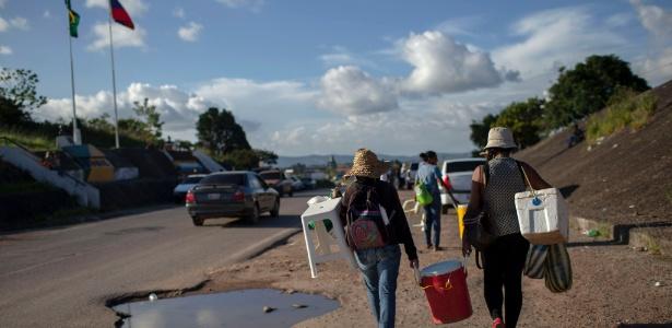 Mulheres venezuelanas voltam a seu país depois de um dia vendendo refrigerantes e salgadinhos na fronteira brasileira de Pacaraima. A cidade é um dos principais pontos de entrada de refugiados no país - Mauro Pimentel/AFP