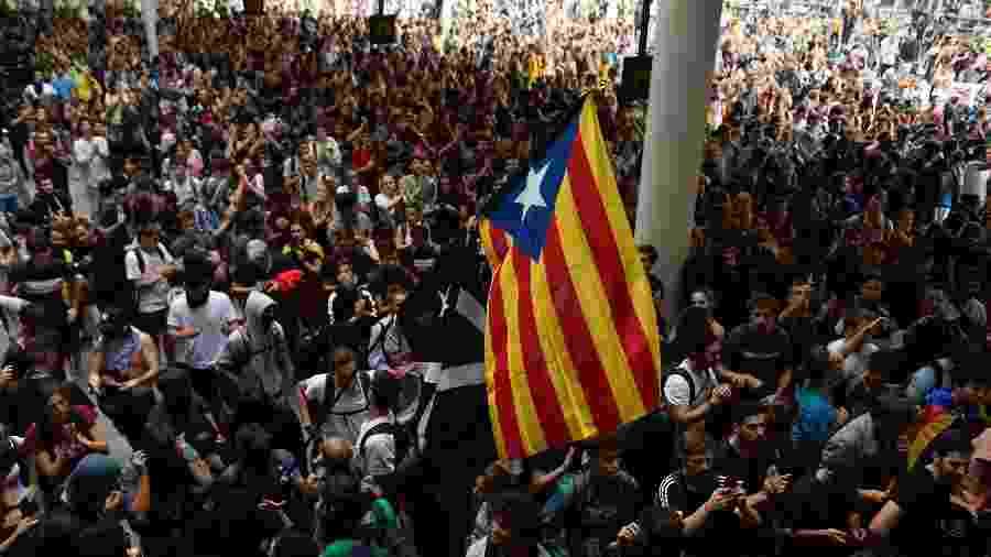 Multidão com bandeira independentista toma acesso do aeroporto de El Prat, em Barcelona - Josep Lago / AFP