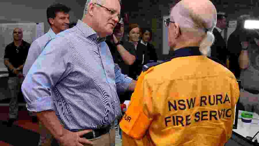 O primeiro-ministro da Austrália, Scott Morrison, visita uma das sedes dos bombeiros em Sydney, após ser criticados por viajar enquanto o pais enfrenta graves incêndios florestais - AAP Image