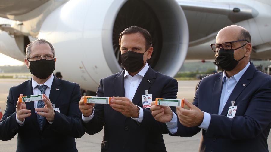 Jean Gorinchteyn (esq.), secretário estadual de Saúde, o governador João Doria (PSDB) e o diretor do Instituto Butantan, Dimas Covas, recebem primeiro lote de insumos da CoronaVac vindo da China no Aeroporto de Guarulhos - Divulgação/Governo de São Paulo