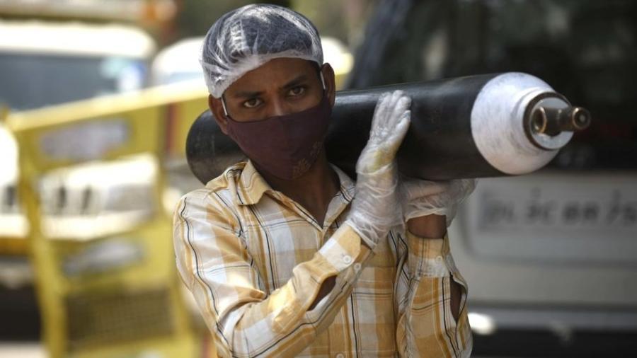 Uma pessoa esperando para reabastecer seu cilindro de oxigênio vazio em Gurjão, Índia; cena aconteceu tanto no Brasil quanto no pais asiático - Getty Images