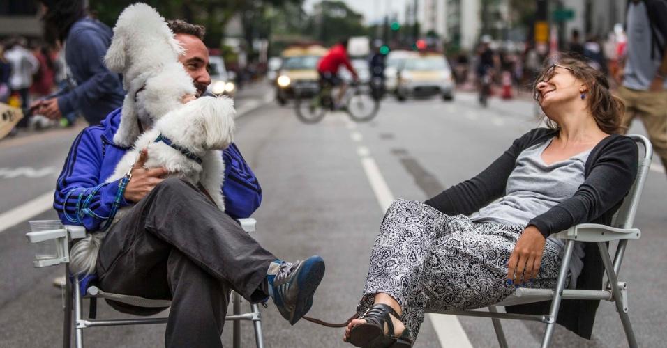 18.out.2015 - Em suas cadeiras no meio da avenida Paulista, casal se diverte com seus cães.  Depois de dois testes realizados em junho e agosto, a prefeitura decidiu fechar a via para carros aos domingos, das 9h às 17h