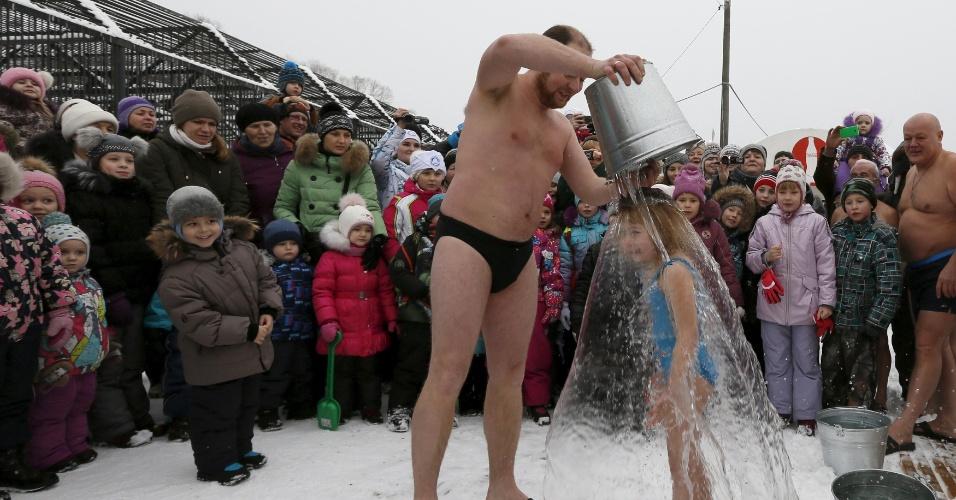 6.jan.2016 - Sob temperatura de -5°C, visitantes observam Grigory Broverman, membro do clube de nadadores de inverno Cryophile, jogar um balde de água gelada na filha Liza, 6, durante um flash mob. A ação faz parte das celebrações do Dia do Urso Polar, no zoológico de Royev Ruchey, no subúrbio siberiano da cidade de Krasnoyarsk, na Rússia. A imagem é do dia 25 de novembro, mas foi divulgada hoje