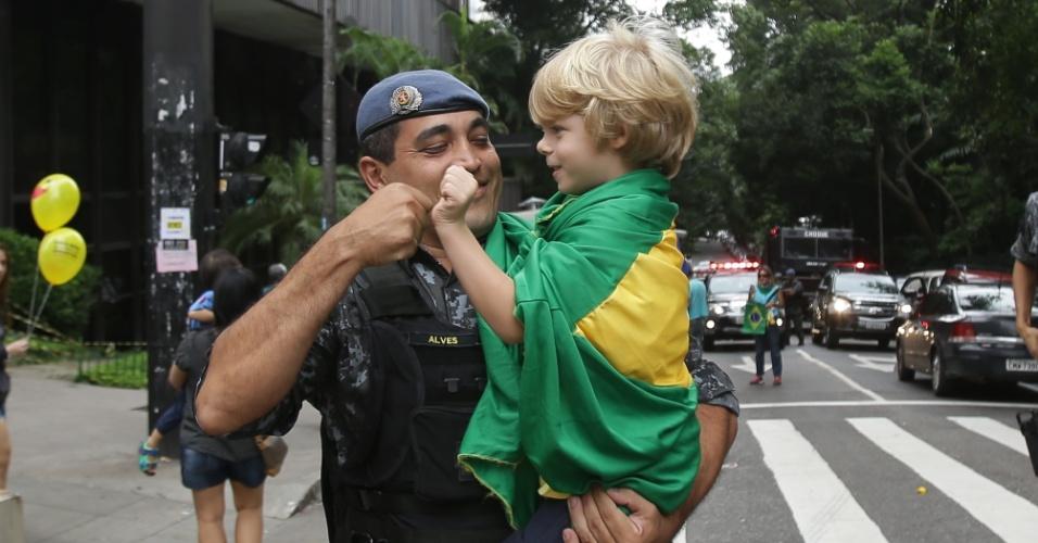 Policial militar interage com criança durante ato contra o governo Dilma Rousseff na avenida Paulista, região central de São Paulo. Os manifestantes pedem o impeachment de Dilma e a prisão do ex-presidente Luiz Inácio Lula da Silva, investigado pela Operação Lava Jato