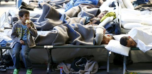 Imigrantes descansam em abrigo temporário em um ginásio esportivo em Hanau, Alemanha