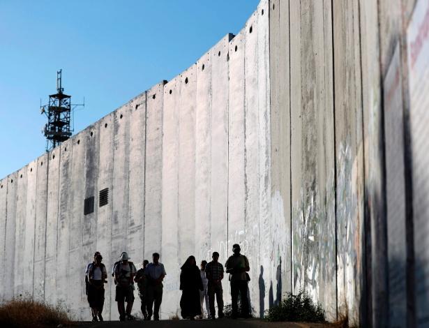 7.jul.2017 - Estrangeiros cristãos caminham ao longo do muro que separa Jerusalém e a Cisjordânia