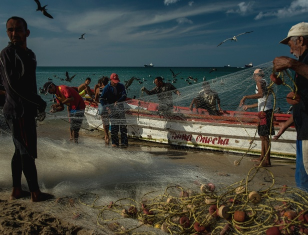 Pescadores descarregam barcos em Amuay, na Venezuela - Meridith Kohut/The New York Times