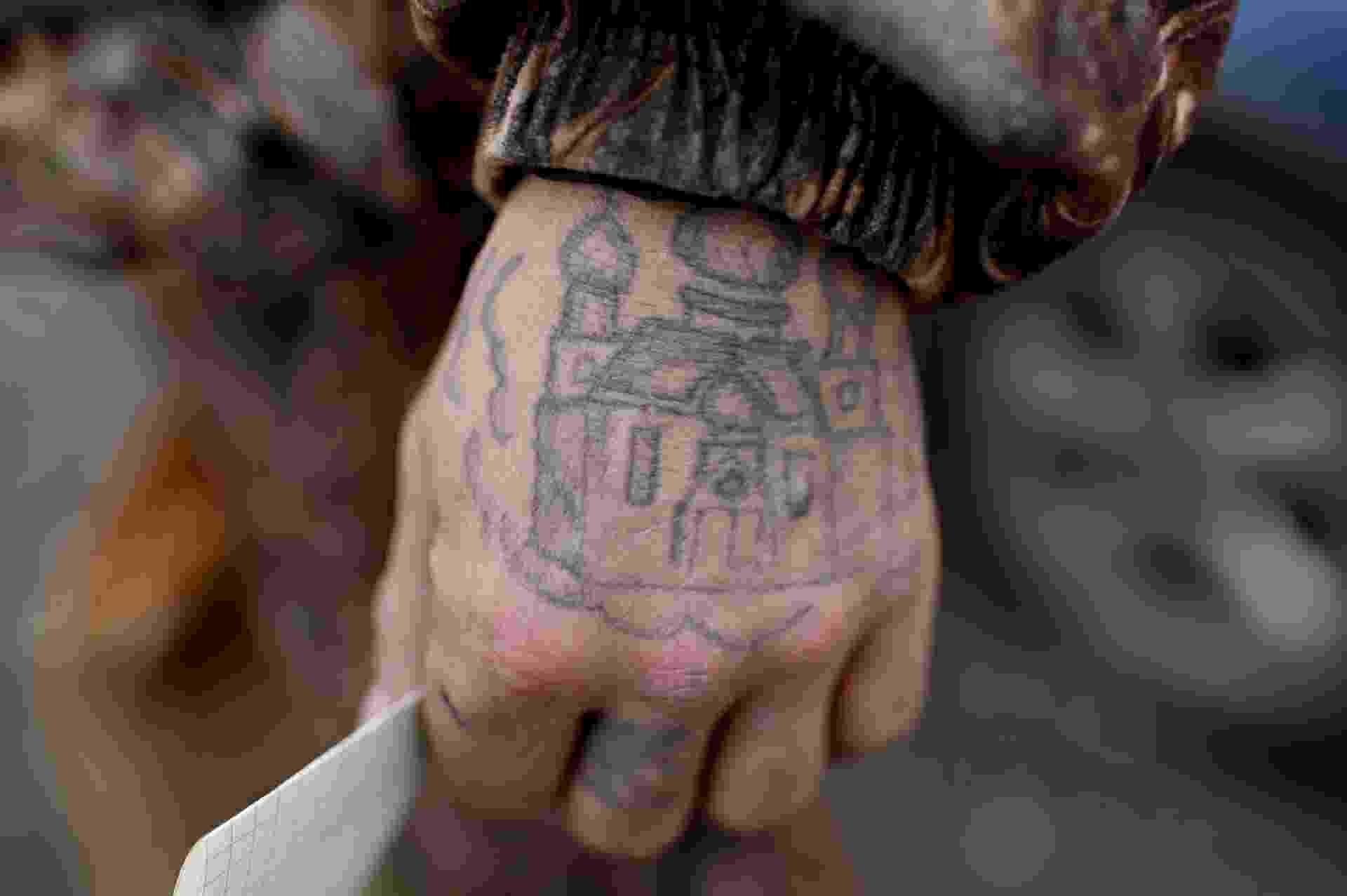 Um homem sem-teto e sua tatuagem de uma igreja ortodoxa na mão segura um pedaço de papel durante evento de caridade organizado pela Caritas - Alexey Malgavko/Reuters