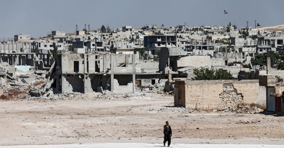 22.jun.2015 - Um sírio caminha próximo a edifícios destruídos em Kobane, na Síria, nesta segunda-feira (22). A Turquia abriu a fronteira em direção a Tal Abyad, no norte da Síria, permitindo que centenas de refugiados regressassem aos seus lares em uma área retomada pela milícia curda, que estava em controle do Estado Islâmico