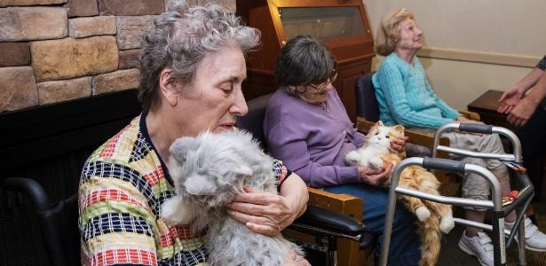 Moradoras da ala de cuidados da memória do Hebrew Home, em Riverdale, Nova York, Lou Ann Wyckoff (à esq.), 79, e Kate Kaye, 99, acariciam gatinhos-robô
