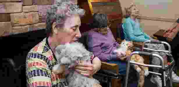 Moradoras da ala de cuidados da memória do Hebrew Home, em Riverdale, Nova York, Lou Ann Wyckoff (à esq.), 79, e Kate Kaye, 99, acariciam gatinhos-robô  - Christian Hansen/The New York Times