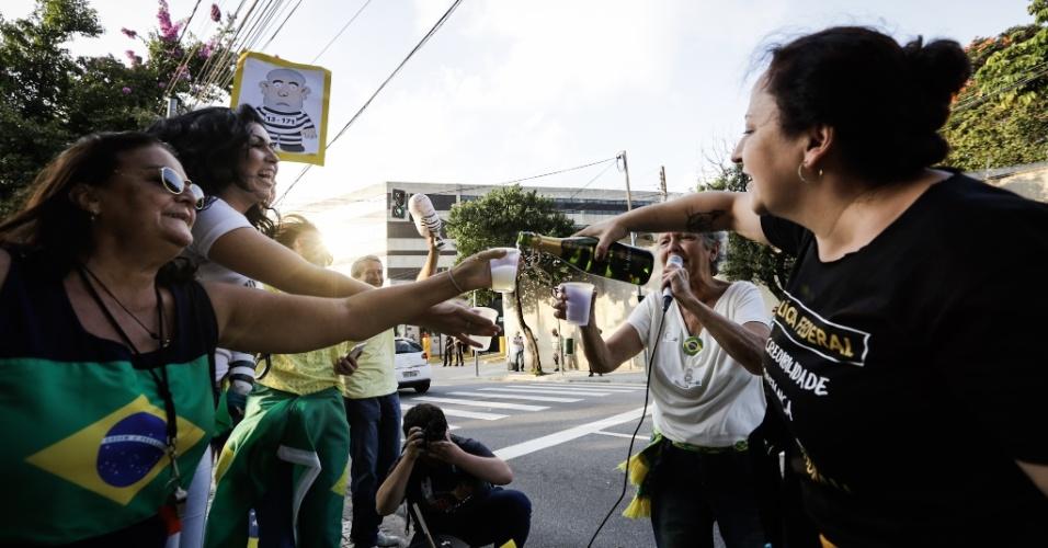 Manifestantes contrários ao ex presidente Lula comemoram a ordem de prisão em frente à Polícia Federal de São Paulo, no bairro da Lapa
