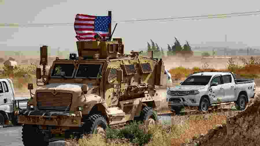 Um soldado dos EUA está sentado no topo de um veículo blindado durante uma manifestação de curdos sírios contra ameaças turcas - Delil Souleiman/AFP