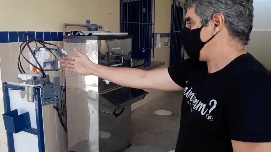 Professor Paulo César ao lado do robô que libera um jato de álcool 70% - Arquivo pessoal