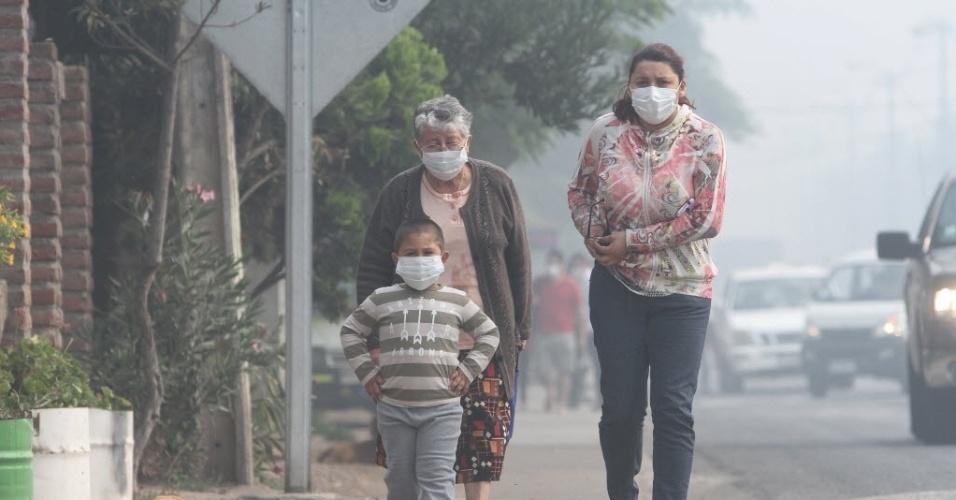19.jan.2016 - Moradores usam máscaras após um incêndio em um tanque de água quente de Santa Marta, em Santiago (Chile). Os sete milhões de habitantes de Santiago enfrentam uma nuvem de fumaça acompanhada por um forte cheiro