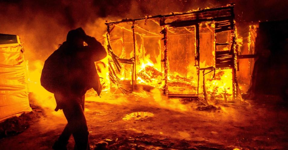 """1º.mar.2016 - Migrante caminha em meio a barracos incendiados no campo de refugiados chamado de """"selva"""", em Calais, na França. Metade da área do campo está sendo desmantelada desde a última segunda (29), o que provoca tensões entre migrantes e autoridades"""